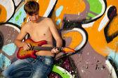 Beautiful brunette boy with guitar near graffiti wall. — Stock Photo