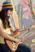 美丽的黑发女孩与吉他和涂鸦墙上的 backgro — 图库照片