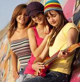Three beautiful girls with guitar and graffiti wall at backgroun — Stock Photo