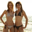 Two beautiful young girlfriends in bikini on the beach at sunris — Stock Photo