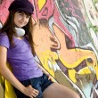 Beautiful brunette girl with headphones and graffiti wall at bac — Stock Photo