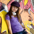 Beautiful brunette girl with headphones and graffiti wall at bac — Stock fotografie