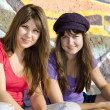 Two girlfriends near graffiti wall. — Stock Photo