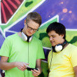 Two friends listening music near graffiti wall. — Stockfoto #6177894
