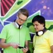 Two friends listening music near graffiti wall. — Stockfoto