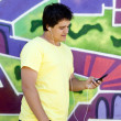 Teen boy with earphones near graffiti wall. — Stock Photo #6178035