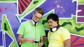 Two friends listening music near graffiti wall. — Stock Photo