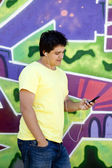 Teen boy with earphones near graffiti wall. — Stock Photo