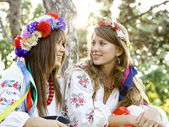 Two girls in national slavic costumes at outdoor. — Stock Photo