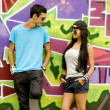 Couple with notebook near graffiti wall. — Stock Photo