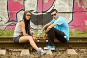 Couple with notebook near graffiti wall. — Stock Photo