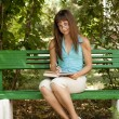 Brunette girl in glasses doing homework at the park. — Stock Photo