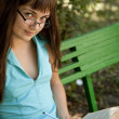 Brunette girl in glasses doing homework at the park. - Stock Photo