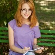 Redhead girl in glasses doing homework at the park. — Stock Photo #6359760