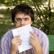 Men with glasses doing homework at the park. - Stock Photo