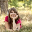 Brunette girl with headphone in the park. — Stock Photo