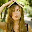 Blonde girl with book over head at the park. — Stock Photo