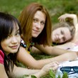 Three girlfriends doing homework at the park. — Stock Photo