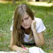 Blonde girl doing homework at the park. — Stock Photo