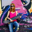 Stock Photo: Style girl with skateboard near graffiti wall.