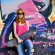 Style girl with skateboard near graffiti wall. - Stock Photo