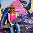 Style girl with skateboard near graffiti wall. — Stock Photo #6397739