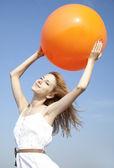 Rude dziewczyny trzymaj piłkę na tle błękitnego nieba. — Zdjęcie stockowe