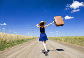 Lonely girl with suitcase at country road. — Stock Photo