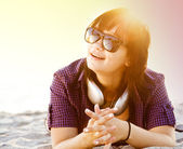 Piękna brunetka dziewczyna ze słuchawkami w piasku na plaży. — Zdjęcie stockowe