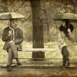 Two sitting at bench in rainy day. Photo in old image style. — Foto Stock