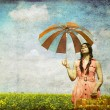 Brunette enchantress with umbrella and suitcase at spring rapese — Stock Photo
