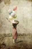 Jeune fille brune avec des ballons de couleur sur fond de ciel bleu. — Photo