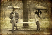 Two sitting at bench in rainy day. Photo in old image style. — Stock Photo