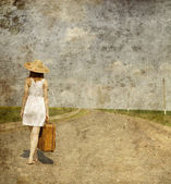 Lonely girl with suitcase at country road.. Photo in old image s — Stock Photo