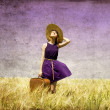 Lonely girl with suitcase at country. - Stock Photo