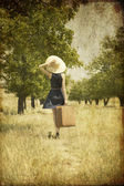 Roodharige meisje met koffer op land. — Stockfoto