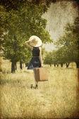 Rusovláska dívka s kufrem na zemi. — Stock fotografie