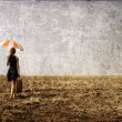 Redhead girl with umbrella at windy field. — стоковое фото #6638927