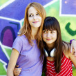Two girls near graffiti wall. - Stock Photo