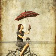 Girl with umbrella on bike. Photo in old image style. — Stock Photo