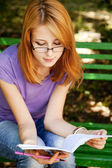 Redhead girl in glasses doing homework at the park. — Stock Photo