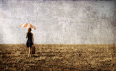 Redhead girl with umbrella at windy field. — Stock Photo