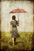 Redhead girl with umbrella at field. — Stock Photo