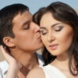 Guy kissing a beautiful girl - Stock Photo