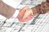 Worker and businessman shaking hands over house renovation plans — Stock Photo