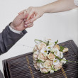 Hands and rings on wedding bouquet - Foto de Stock  
