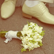 Bride's bouquet and groom's shoe — Stock Photo