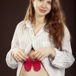 Pregnant woman in a man's shirt with a children's slippers on he — Stock Photo