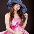 Beautiful pregnant woman in a pink dress and hat — Stock Photo #5391085