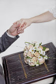 Hands and rings on wedding bouquet — Stock Photo